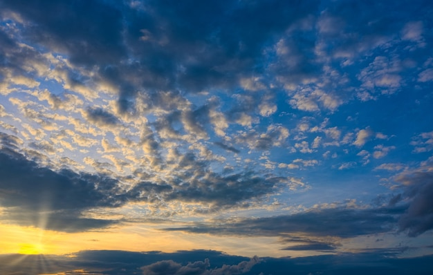 Beautiful sunset with the bright setting sun breaking through clouds Premium Photo
