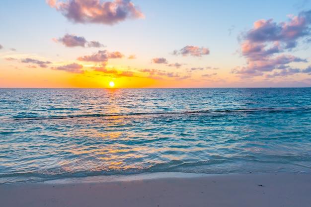 Beautiful sunset with sky over calm sea  in tropical maldives island Premium Photo
