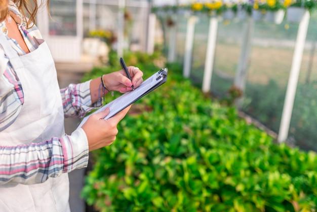 Beautiful supervisor writing on clipboard at plant nursery Premium Photo