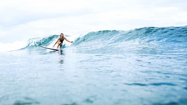 Bella ragazza surfista in sella a una tavola Foto Gratuite