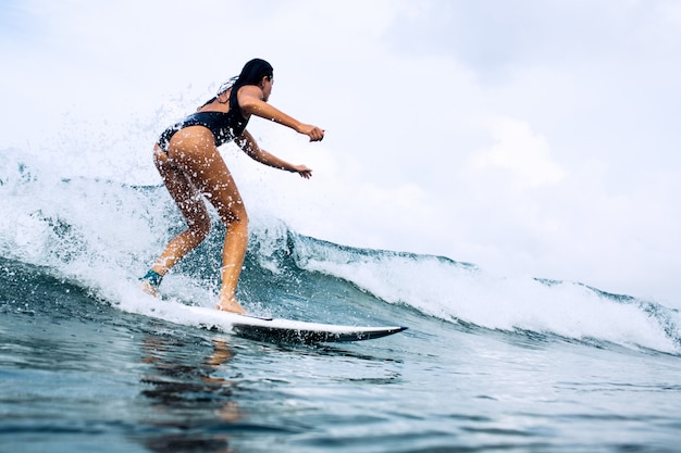 Beautiful surfer girl riding on a board Free Photo