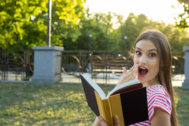 Beautiful surprised woman reading a book Premium Photo