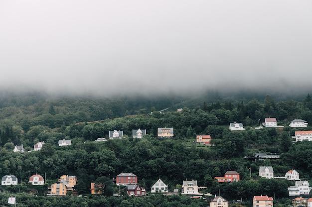 Красивый симметричный снимок разноцветных домов на туманный холм Бесплатные Фотографии