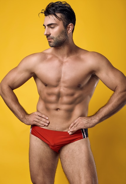 Bello uomo muscoloso abbronzato che indossa un costume da bagno rosso Foto Gratuite