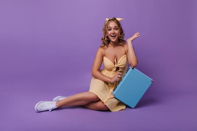 Bella donna abbronzata con sorriso sorpreso divertente in posa con la valigia. ritratto di ragazza stupefacente rilassata in abito luminoso. Foto Gratuite