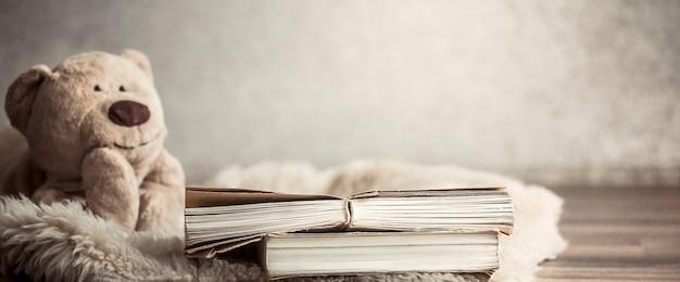 Красивый плюшевый мишка с книгой на полу в уютной гостиной дома Premium Фотографии