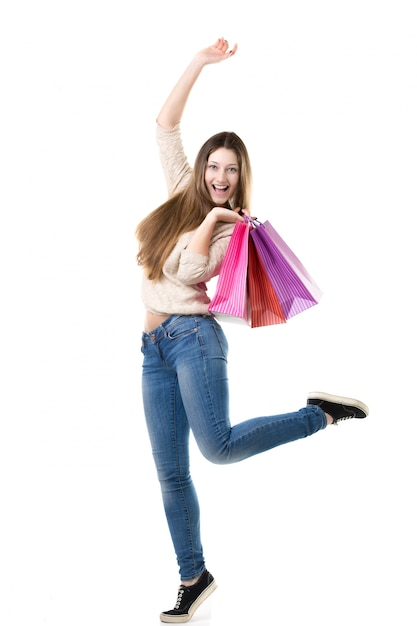 Beautiful teenage girl jumping high with delight holding pink shopping bags Free Photo