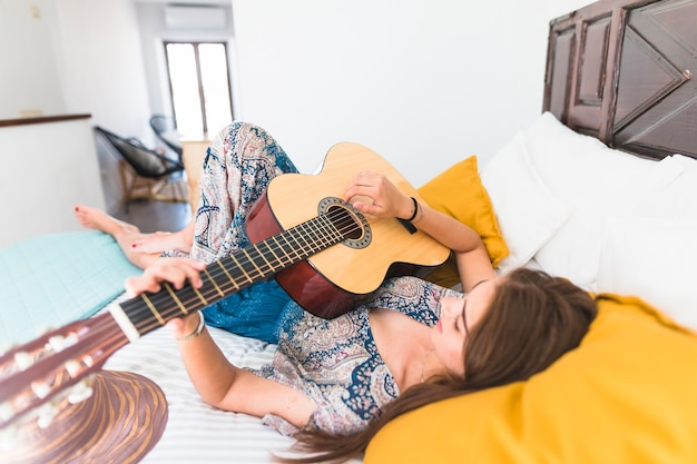 Beautiful teenage girl lying on bed playing guitar Free Photo