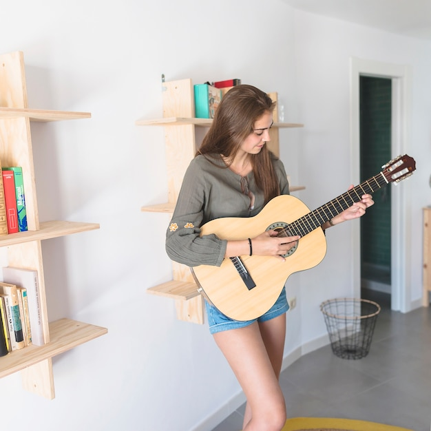 Beautiful teenage girl playing guitar at home Free Photo