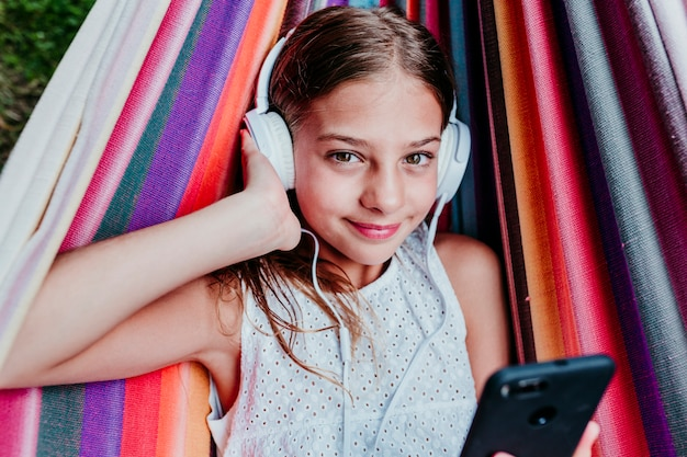 Beautiful Teenager Girl Lying On Colorful Hammock At The Garden Listening To Music On Mobile Phone And Headset And Smiling Relax And Fun Outdoors Premium Photo