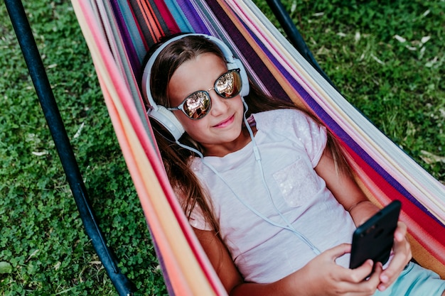 Beautiful teenager girl lying on colorful hammock at the garden. listening to music on mobile phone and headset and smiling.  relax and fun outdoors Premium Photo