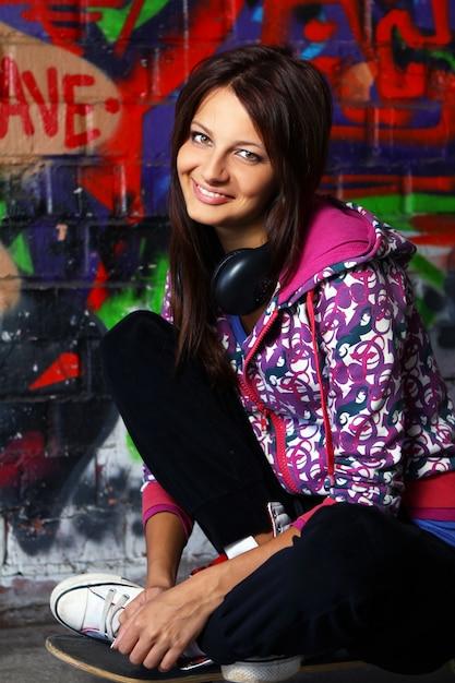 Beautiful teenager girl with headphones sitting on skateboard Free Photo