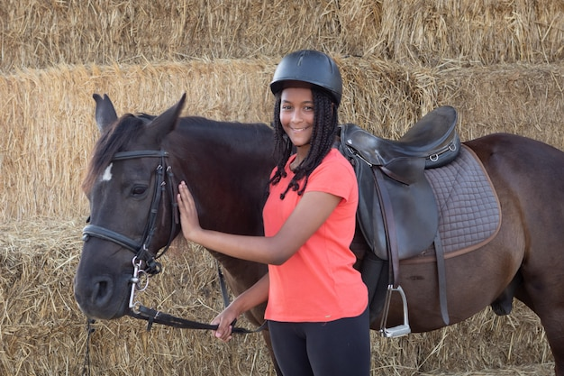 Beautiful teenager with his horse learning to ride Premium Photo