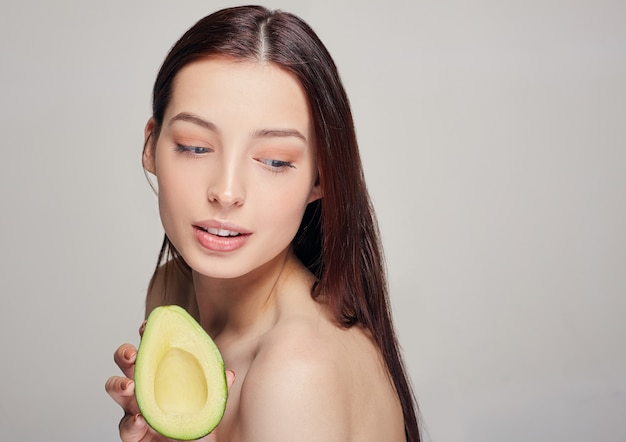 Beautiful tender lady with pure skin with avocado in hand Premium Photo