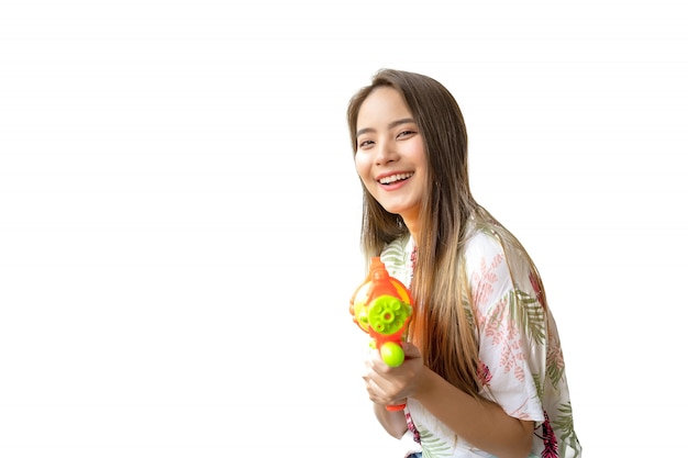 A beautiful thai woman smiling fresh and happy, in her hand holding a water gun in the thai songkran festival on a white background. Premium Photo