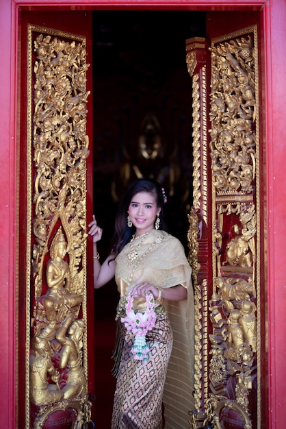 Beautiful thai woman in traditional dress costume, temple thailand Free Photo