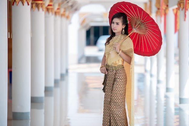 Beautiful thai woman in traditional dress costume at temple of thailand Free Photo
