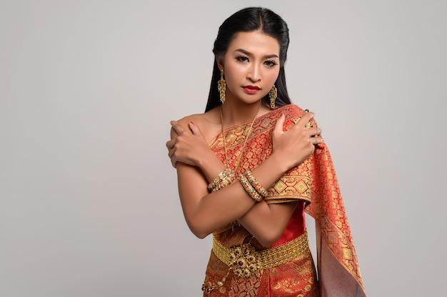 Beautiful thai woman wearing thai dress and standing hugging herself Free Photo