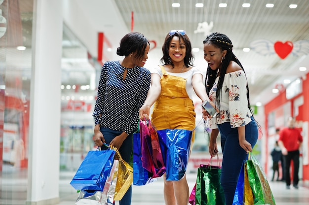 Beautiful three well-dressed afro american girls customers with colored shopping bags at mall. Premium Photo