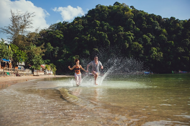 Beautiful tourist young couple holding hands together running along the beach shore with mountains and blue sea water and sky, outdoors, create splashes. lifestyle travel and tourism, honeymoon Premium Photo