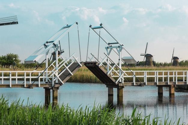 Beautiful traditional dutch windmills near water channels with drawbridge Free Photo