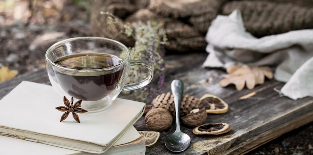 Beautiful transparent cup of tea with autumn leaves and dried lemon on a wooden pallet on nature background Free Photo