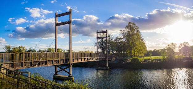 イギリス、ウィンザーの日没で川に架かる橋のある公園の美しい木 無料写真
