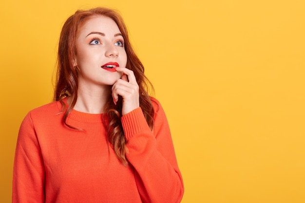 Beautiful trendy girl in orange sweater being deep in thoughts Free Photo