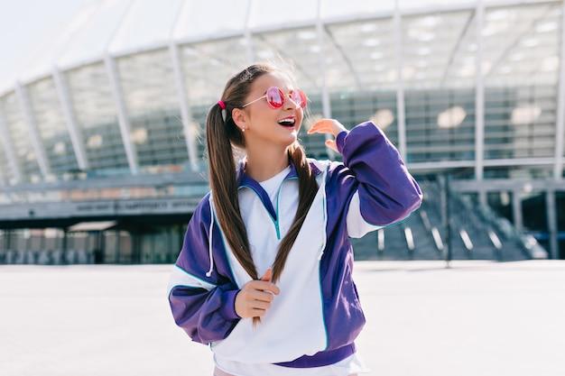 ピンクのサングラスをかけて笑っているスタイリッシュな服を着た美しいトレンディな若い女性 無料写真