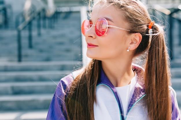 ピンクのサングラスと笑顔のスタイリッシュな服を着た美しいトレンディな若い女性 無料写真