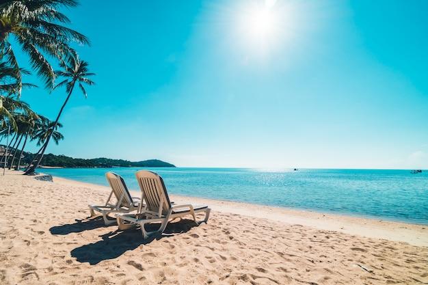 푸른 하늘에 의자가있는 아름다운 열대 해변과 바다 무료 사진
