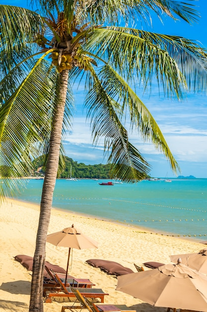 Beautiful tropical beach sea and ocean with coconut palm tree  and umbrella and chair on blue sky Free Photo