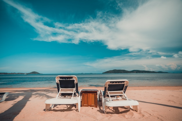 Beautiful tropical beach and sea with coconut palm tree and chair in paradise island Free Photo