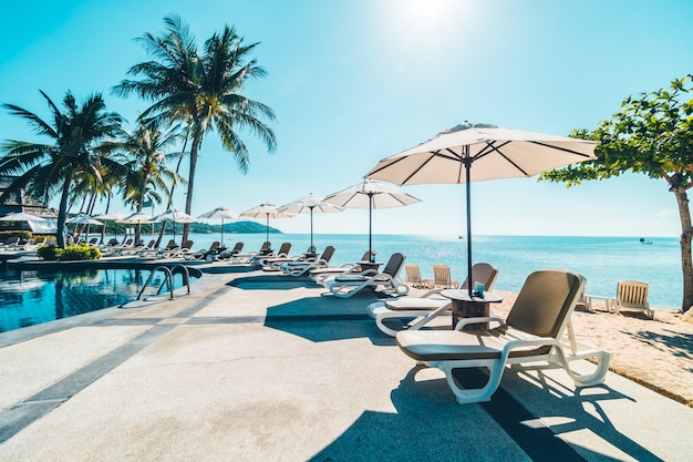 Beautiful tropical beach and sea with umbrella and chair around swimming pool Free Photo