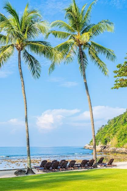 青い空に白い雲とビーチの海の周りの椅子と椅子と美しい熱帯のココヤシの木 無料写真