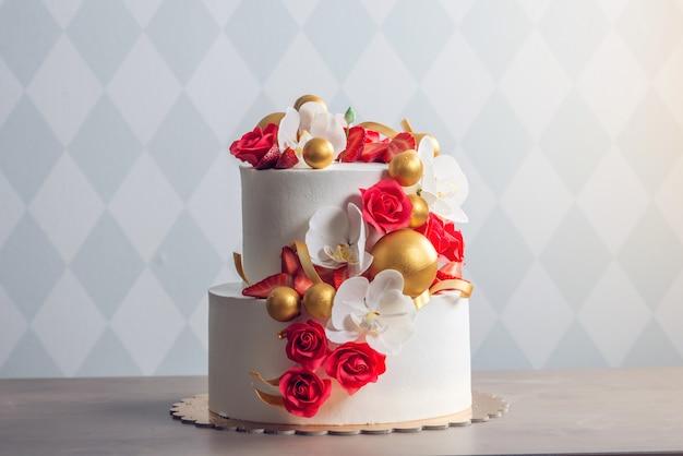 赤いバラで飾られた美しい2段白いウェディングケーキ Premium写真