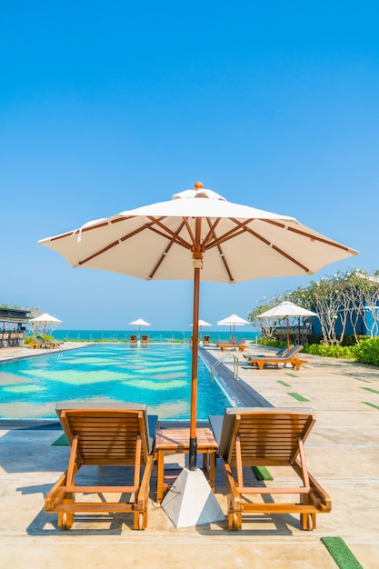 Beautiful umbrella and chair around swimming pool in hotel and resort Free Photo