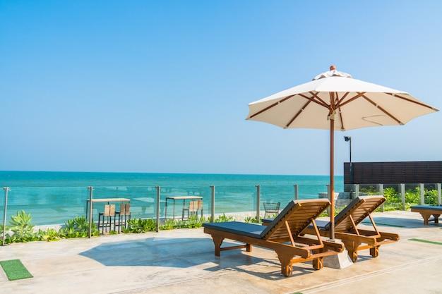 Beautiful umbrella and chair around swimming pool in hotel and resort Free Photo