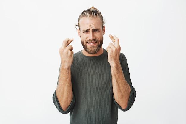 指を保持している美しいひげを剃っていない男が心配そうな表情と交差 無料写真