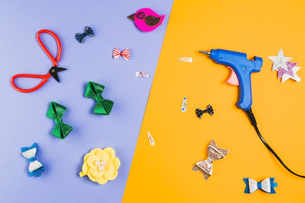 Beautiful various hair clip with scissor and hot glue gun over dual background Free Photo