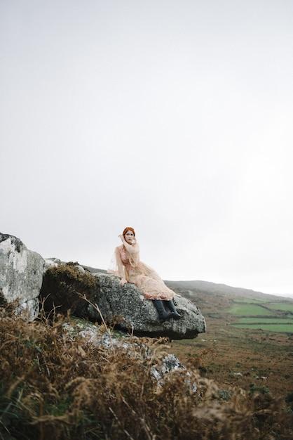 魅力的なピンクのガウンで真っ白な肌を持つ生姜の女性の美しい垂直画像 無料写真