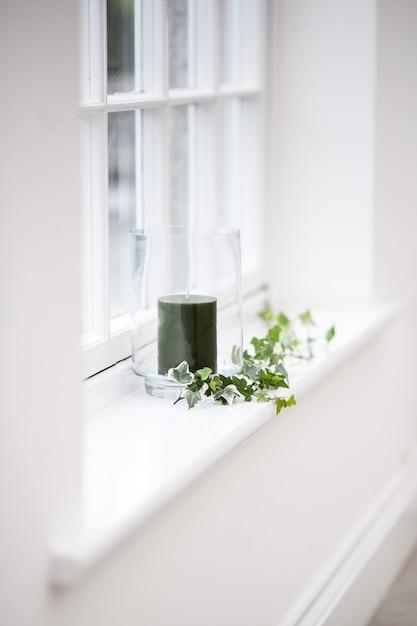 창 선반에 나뭇잎으로 장식 된 유리에 검은 촛불의 아름다운 세로 샷 무료 사진