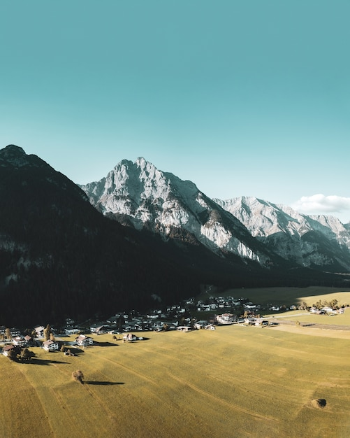 Bella ripresa verticale del piccolo paese situato nelle alpi Foto Gratuite