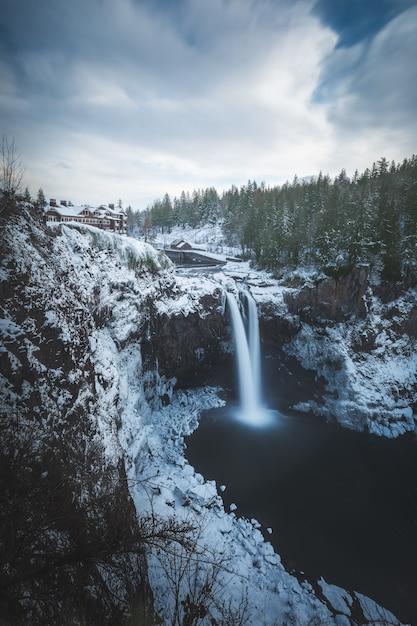 Bello colpo verticale delle cascate sulla montagna del ghiacciaio vicino agli alberi in inverno Foto Gratuite
