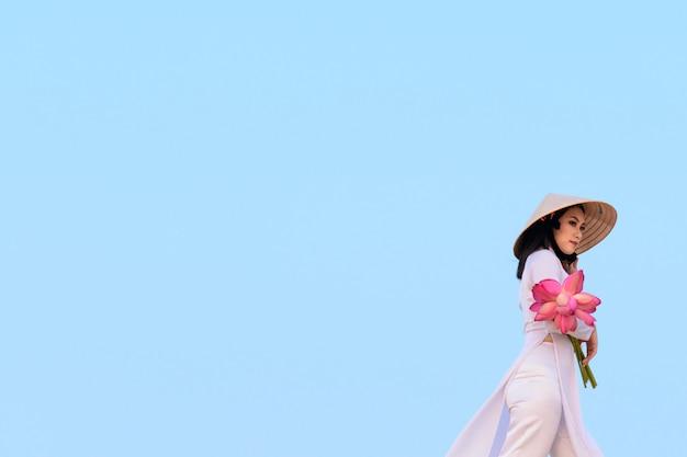 Beautiful vietnamese holding pink lotus in white sand dune desert, muine, vietnam Premium Photo