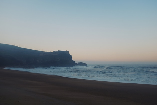 Bella vista di una grande roccia con un castello in cima e grandi onde che avvisano del tramonto Foto Gratuite