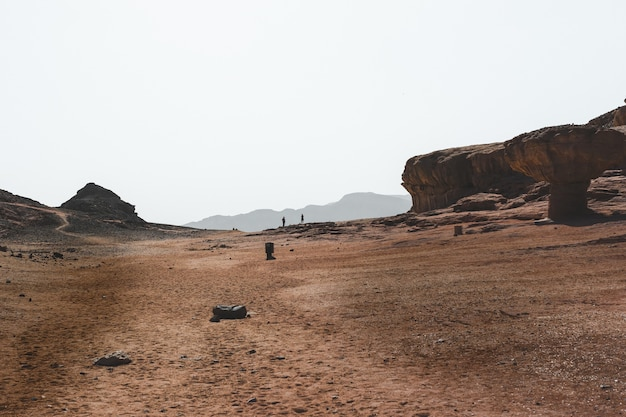 Bella vista sulle grandi rocce e dune in un deserto con le montagne sullo sfondo Foto Gratuite