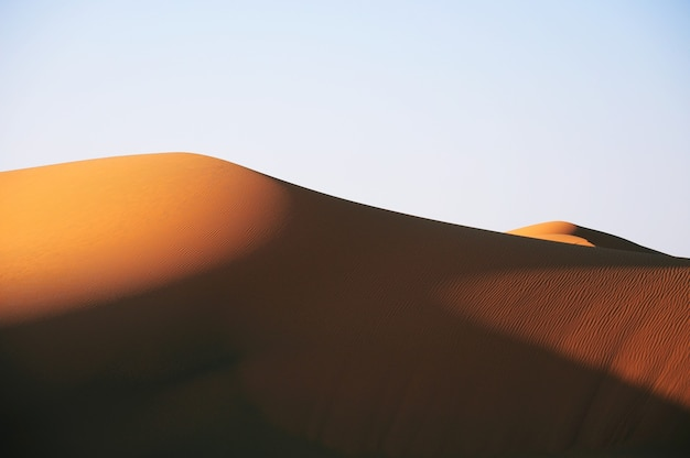 Bella vista di un deserto durante il tramonto sotto un cielo azzurro Foto Gratuite