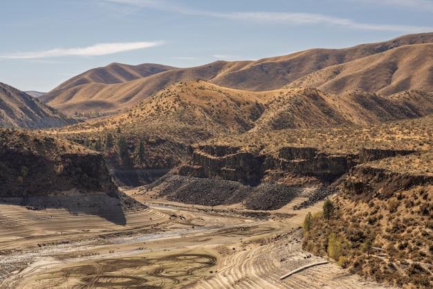 Bella vista delle montagne del deserto coperte di cespugli secchi con un cielo blu Foto Gratuite