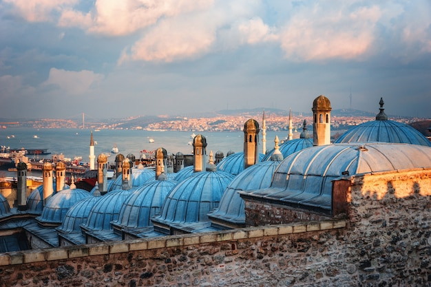 Beautiful view of the golden horn at sunset, istanbul, turkey. the roofs of the suleymaniye mosque in the rays of the setting sun against the blue sea in istanbul Premium Photo